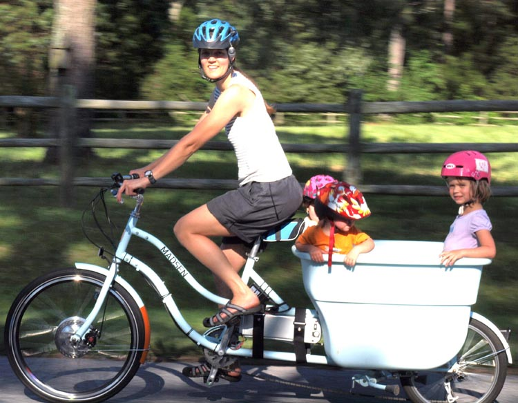Electric bikes make it possible for parents to transport their kids on bikes, not in minivans. Are we going to tell this mom to get out of the f---ing bike lane? Photo of Elise Madsen and her children on an electric cargo bike from this blog