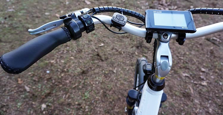 The rear bike light includes remote wireless left and right turn signal indicators. You can see the remote controller to the left of the LCD display. Also notice the beautiful stitched leather hand grips. Ampere electric bike review