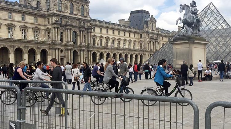 Our electric bike tour group cycling past the iconic pyramid of the Louvre in Paris