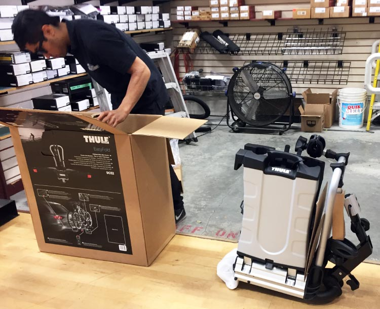 The Thule 9032 Easy Fold Electric Bike Rack is fully assembled in the box, so there is pretty much nothing to do. In this photo, the salesman has just lifted the ready-to-go bike rack out of the box