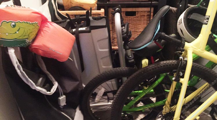 We can fold our Thule 9032 Easy Fold Electric Bike Rack up like a suitcase, carry it upstairs, and slide it into the corner of our laundry room. Can you even spot it here?