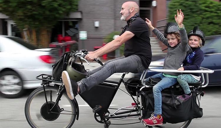 Electric bikes make it possible for most people to cycle – and have fun! – even if they have heavy loads to transport, such as children or groceries. This is one of the reasons why ebikes cause people to cycle more. This is a family on the Morrison Electric Cargo Bike, which you can read about here