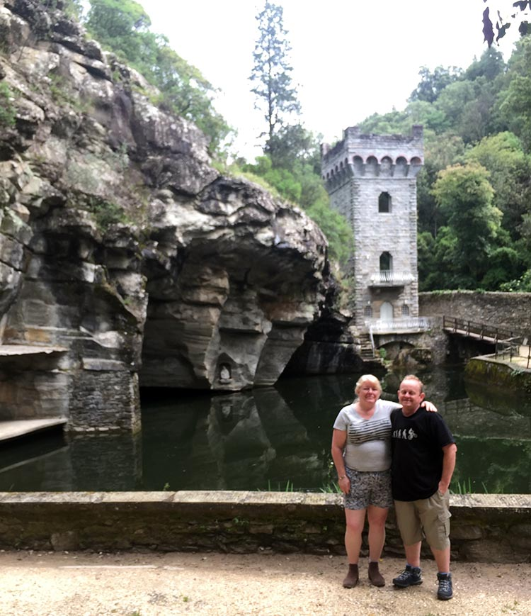 Our Electric Bike tour of Florence: Maggie and I next to the miniature castle turret over a pond in a quarry, in the Laghetto delle Colonne